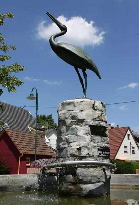 Steinbrunnen mit Schwanskulptur