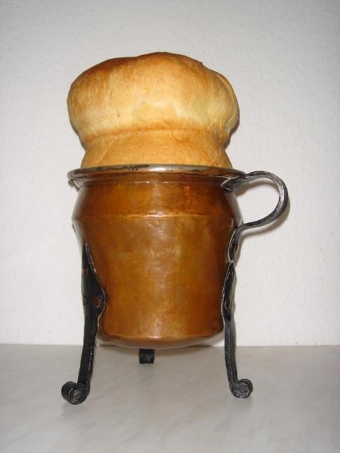 runde, auf drei Beinen stehende Kupferbackform mit Hefegebäck