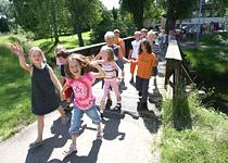 Kinder laufen aus der Schule und winken
